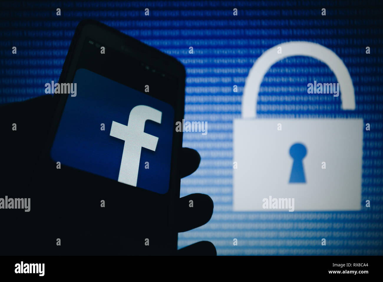 Facebook icon, logo is shown on smartphone display, open lock, numbers zero, one as a texture, blue gradient unfocused on background - Stock Image