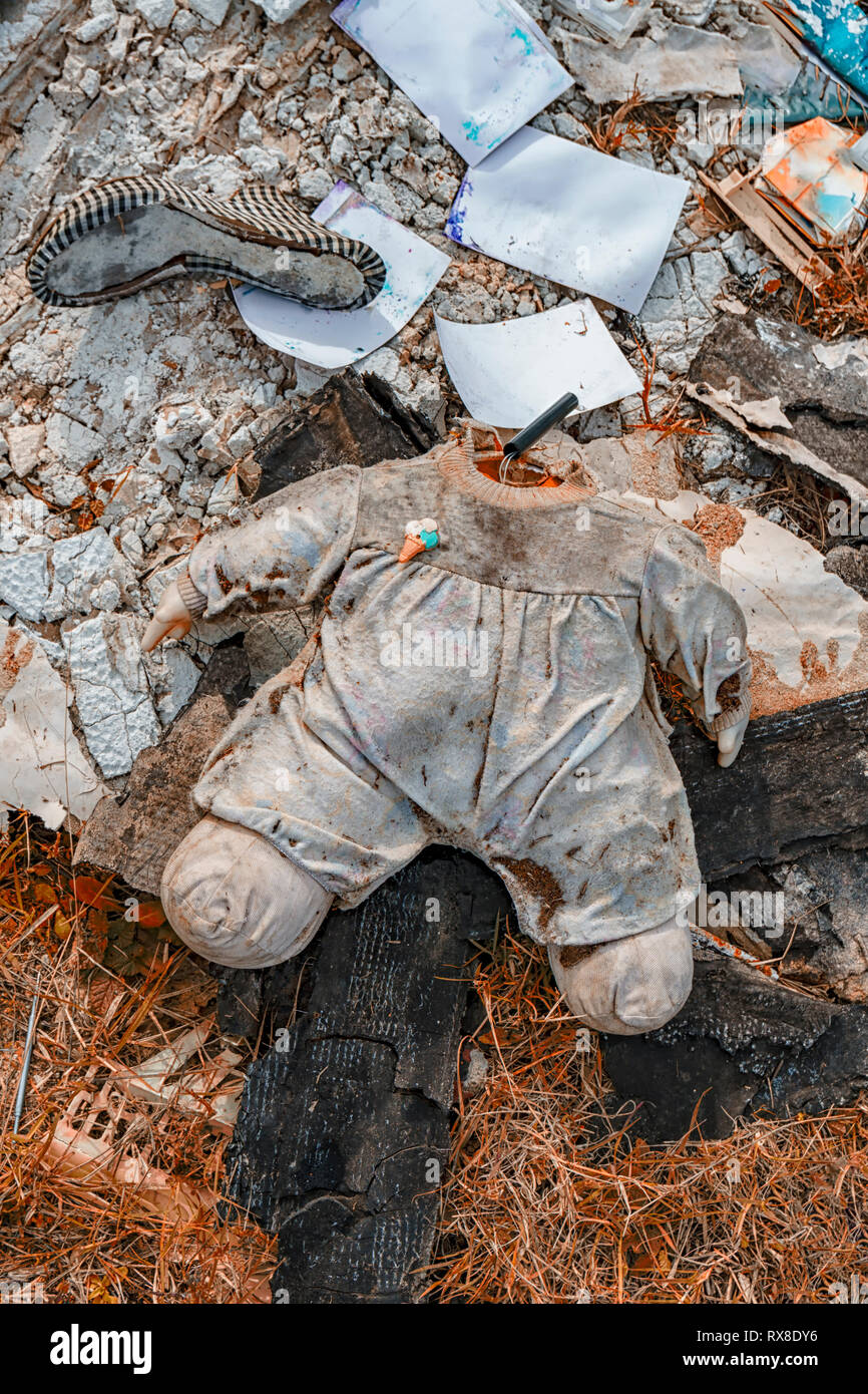 Body of a doll without a head distressing lying in a landfill with other waste. - Stock Image