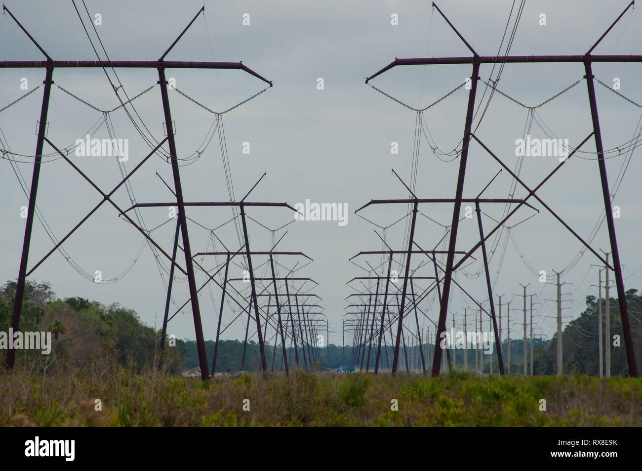 field of electric power cable towers in a line and cloudy sky - Stock Image