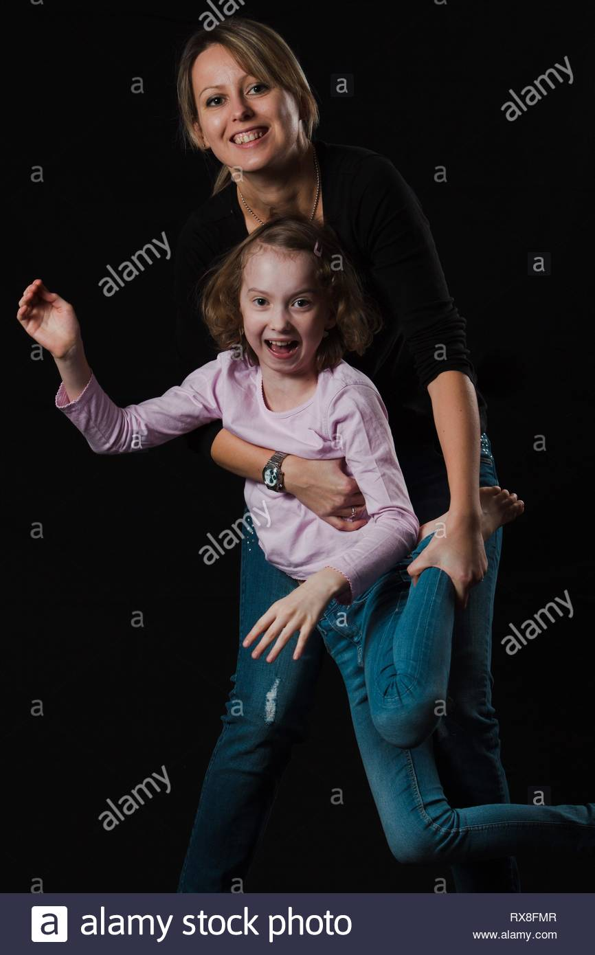 Smiling mother with blond daughter posing on black background. Naturally processed photo with natural look and skin. - Stock Image