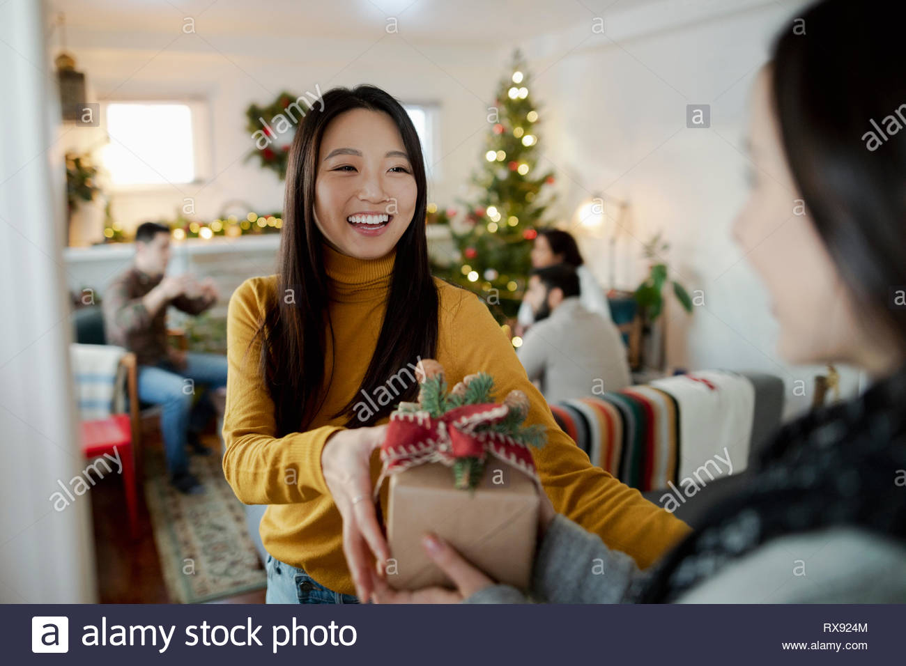 Happy young woman greeting friend with christmas gift in doorway - Stock Image