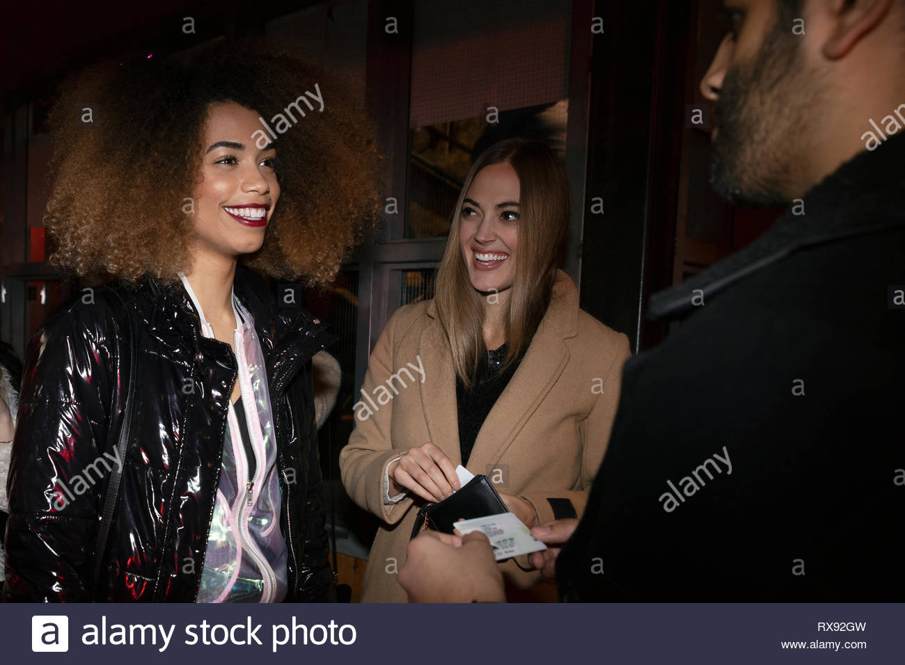Women friends showing IDs to nightclub bouncer - Stock Image