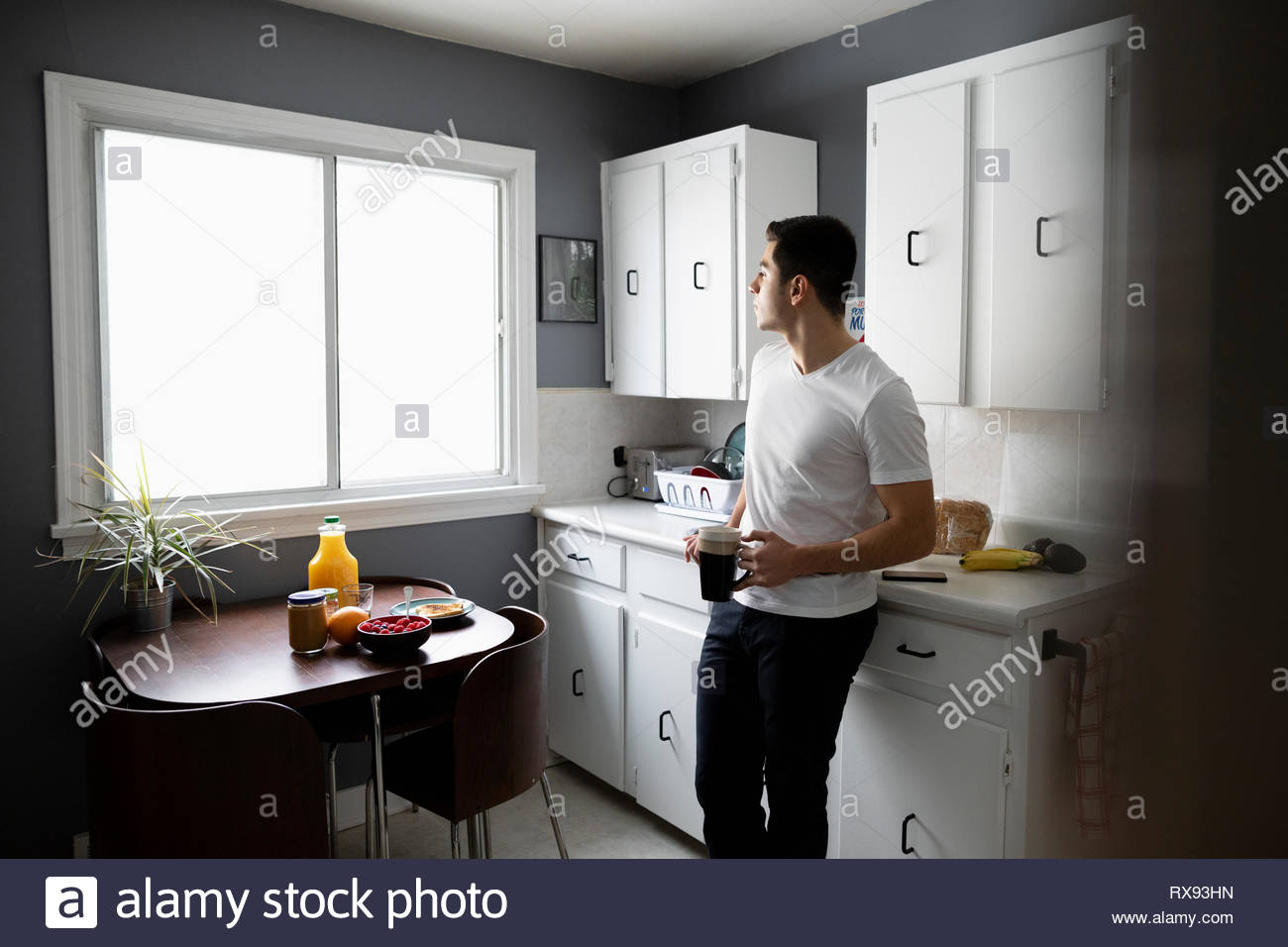 Thoughtful young Latinx man drinking coffee in morning kitchen - Stock Image