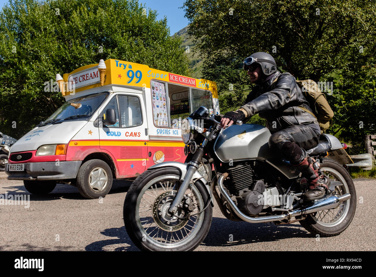 A motorcyclist passes ice cream van parked during sunny summer weather in the scottish highlands, glen nevis fort william scotland uk - Stock Image