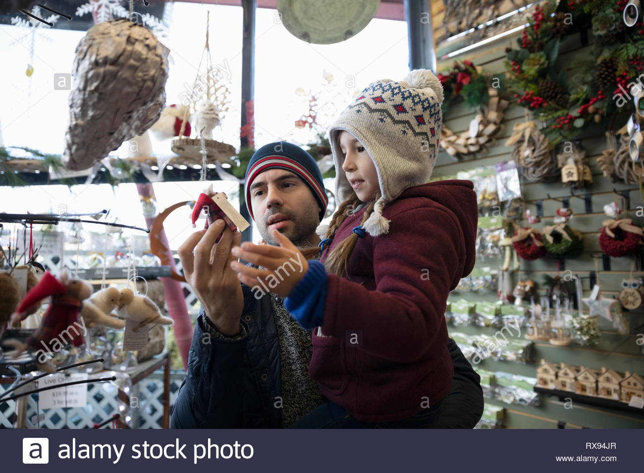 Father and daughter shopping for christmas ornaments at market - Stock Image