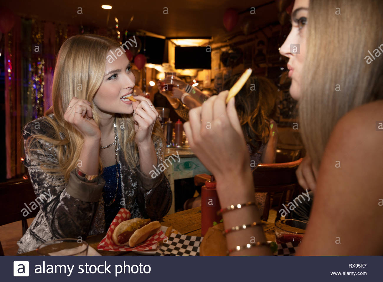Women friends eating at late night diner - Stock Image