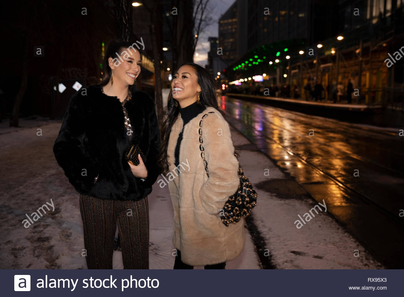 Women friends on snowy urban street at night - Stock Image
