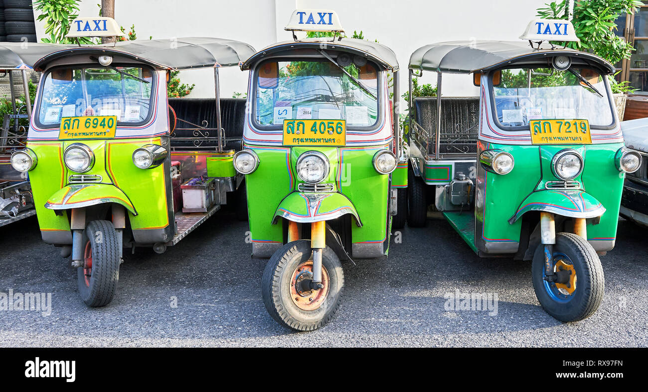 Bangkok, Thailand: Close-up panorama view of three isolated green colored Tuk-Tuk vehicles parking in front of a white wall without persons Stock Photo