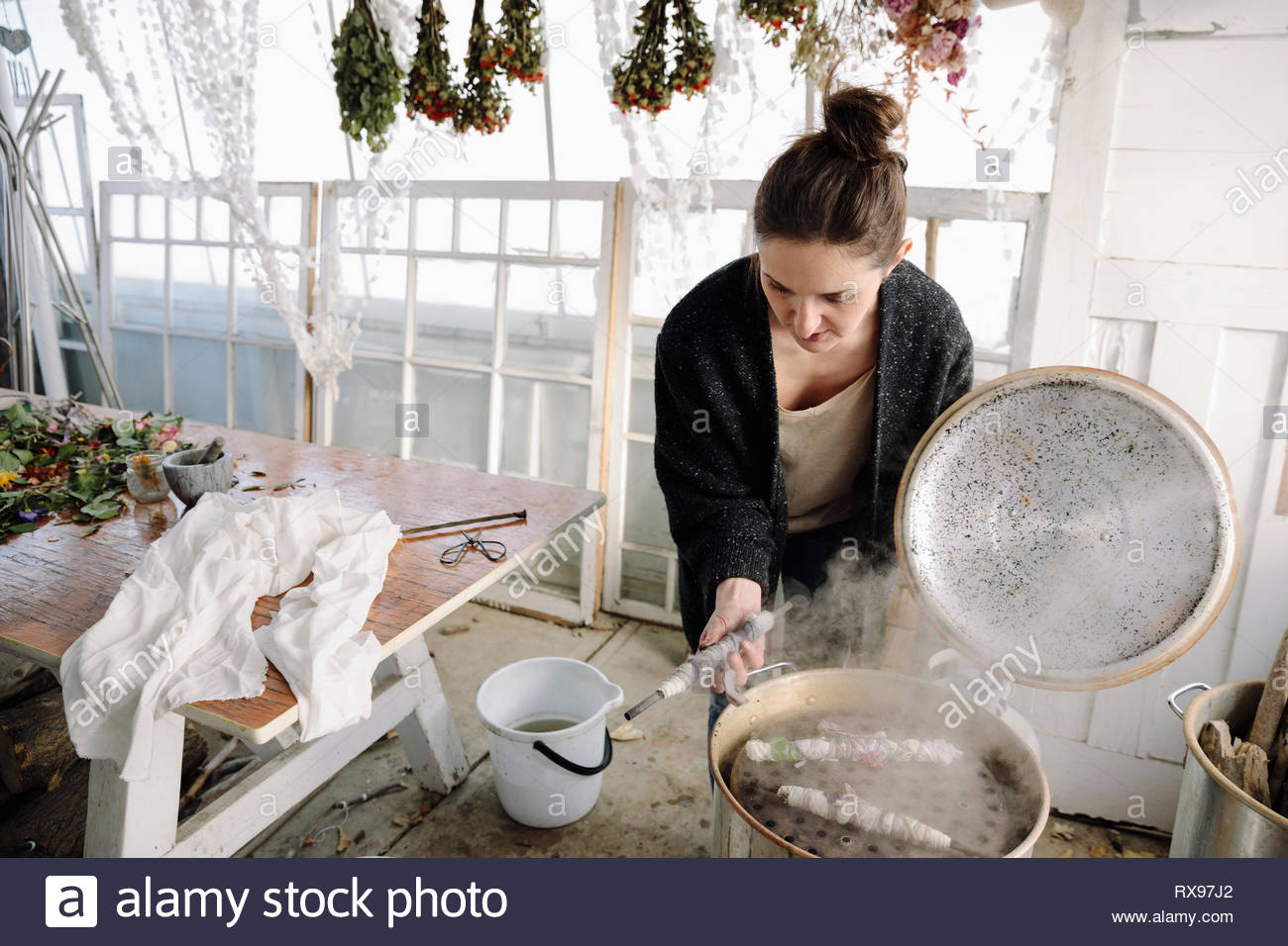 Woman drying flowers for paper making - Stock Image
