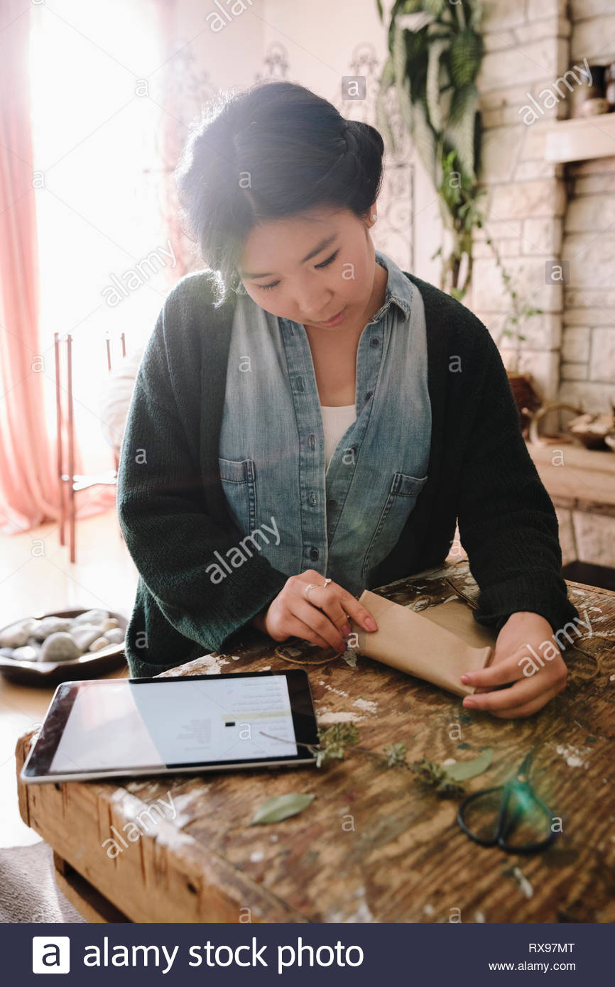 Creative female artist with digital tablet wrapping package - Stock Image