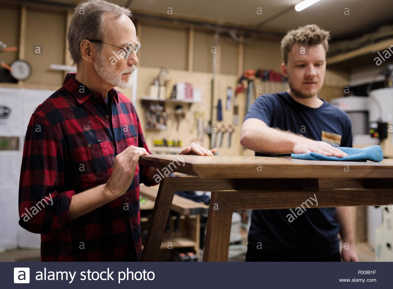 Father and son carpenters finishing bench in workshop - Stock Image