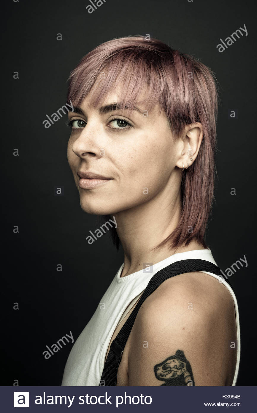 Portrait confident beautiful non-binary gender person with pink hair - Stock Image