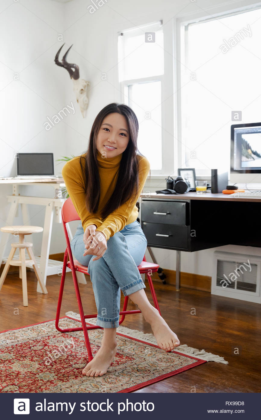 Portrait confident young woman working in home office - Stock Image