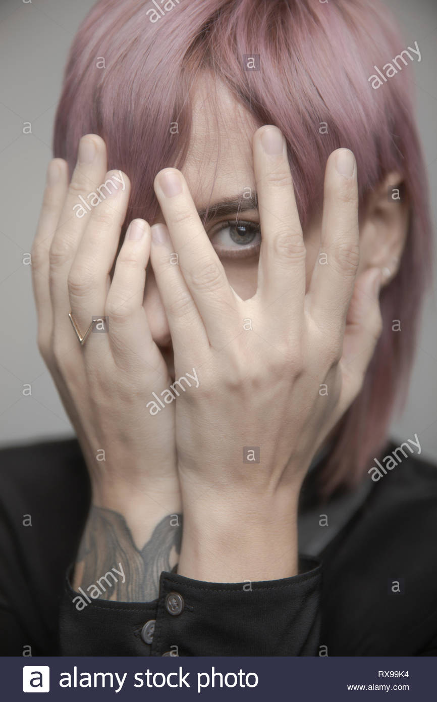 Portrait beautiful non-gender person with pink hair hiding head in hands - Stock Image