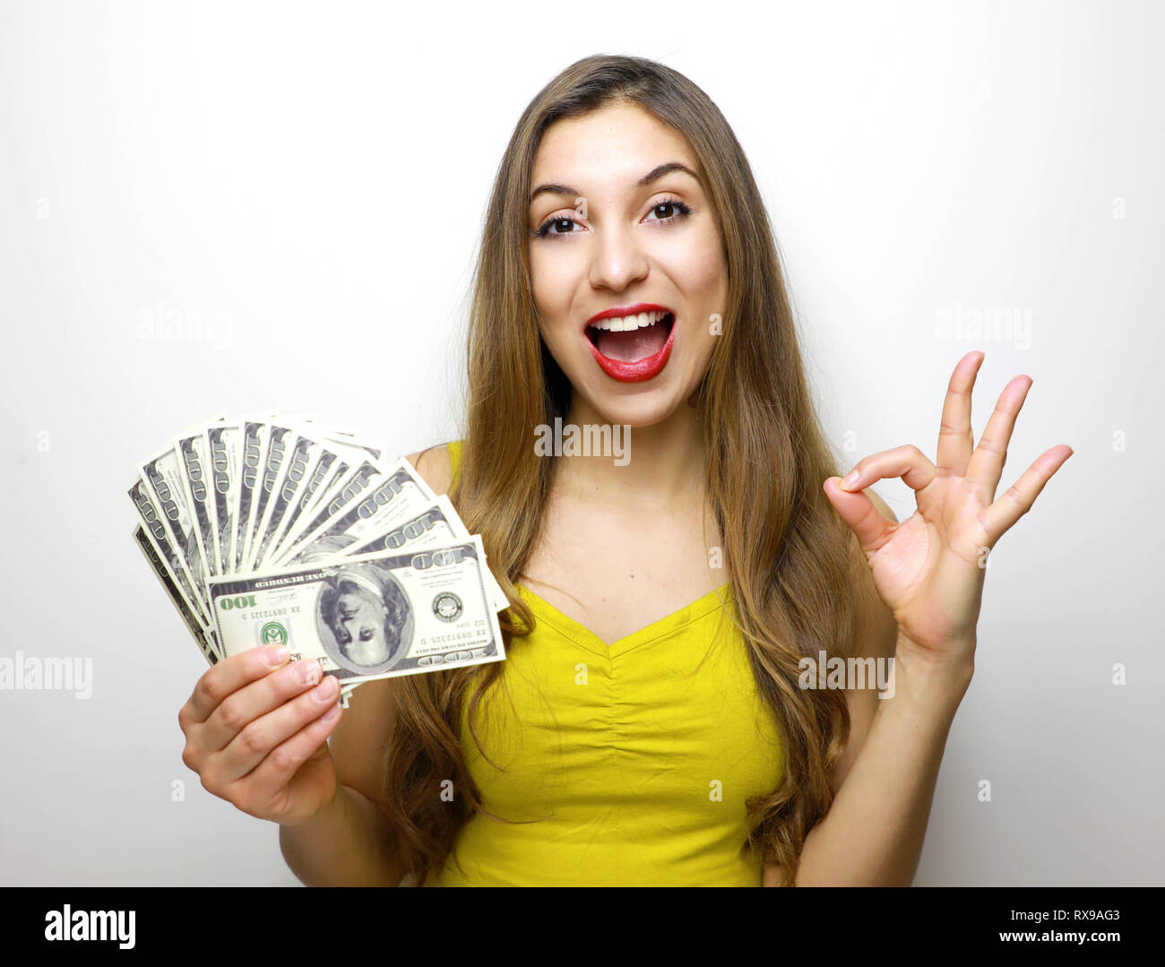 Successful american woman holding fan of money dollar bills and showing ok sign isolated over white background - Stock Image