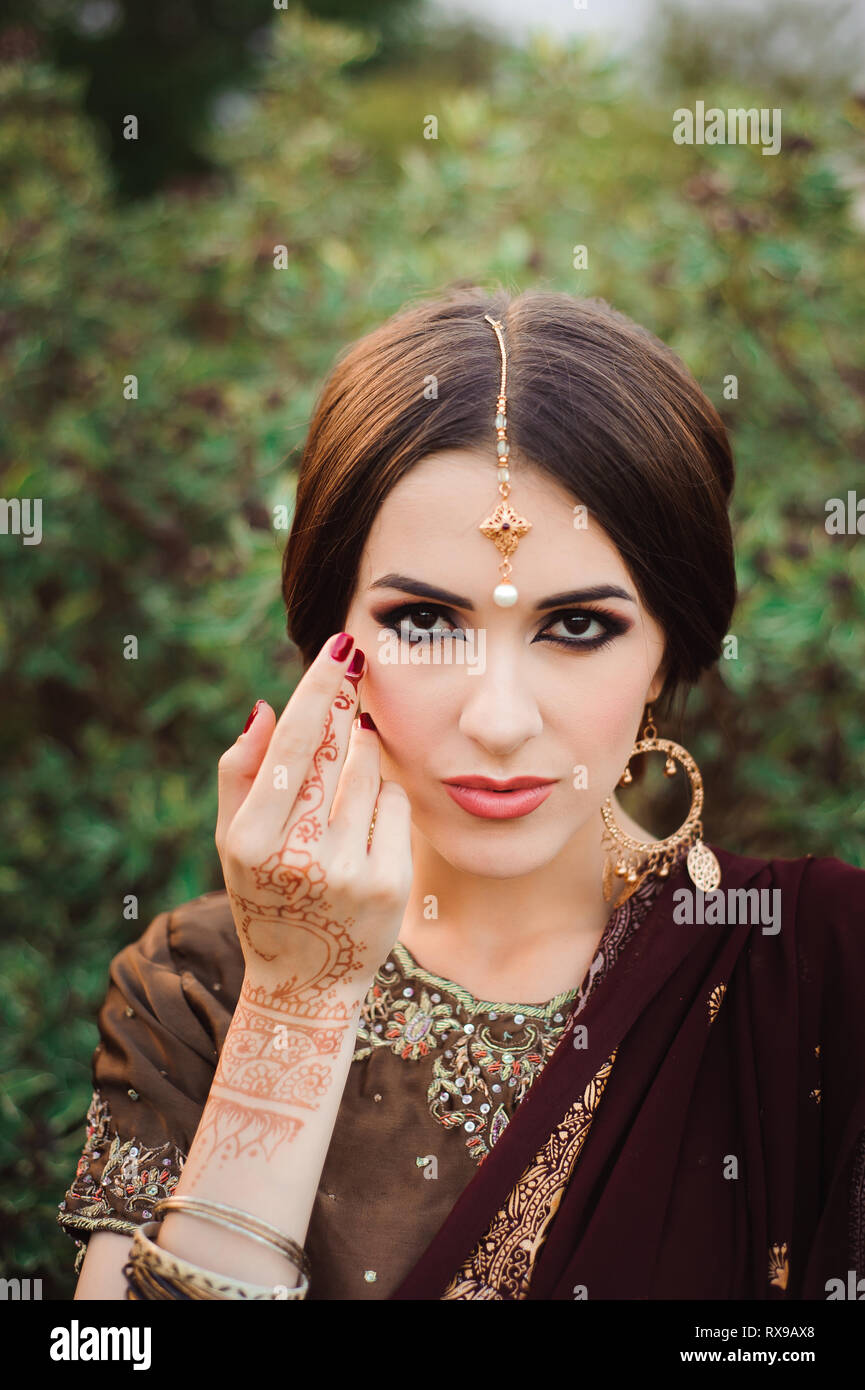 Mehendi on the hands of girls, Woman Hands with brown mehndi tattoo. Hands of Indian bride girl with brown henna tattoos - Stock Image