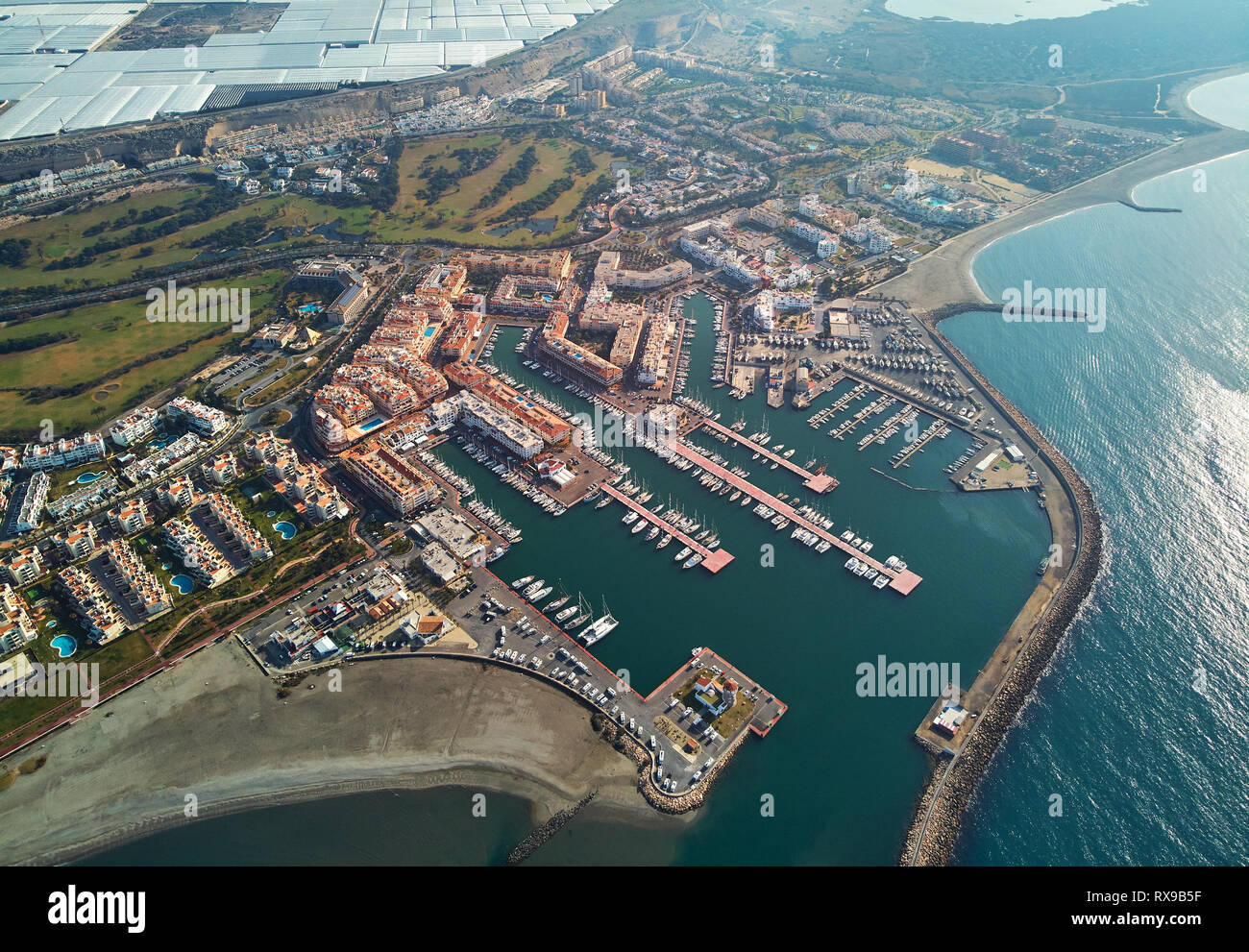 Aerial drone point view panorama of Almerimar townscape, greenhouses,  moored nautical vessels in the harbor, coastline sandy beach, Spain Stock Photo