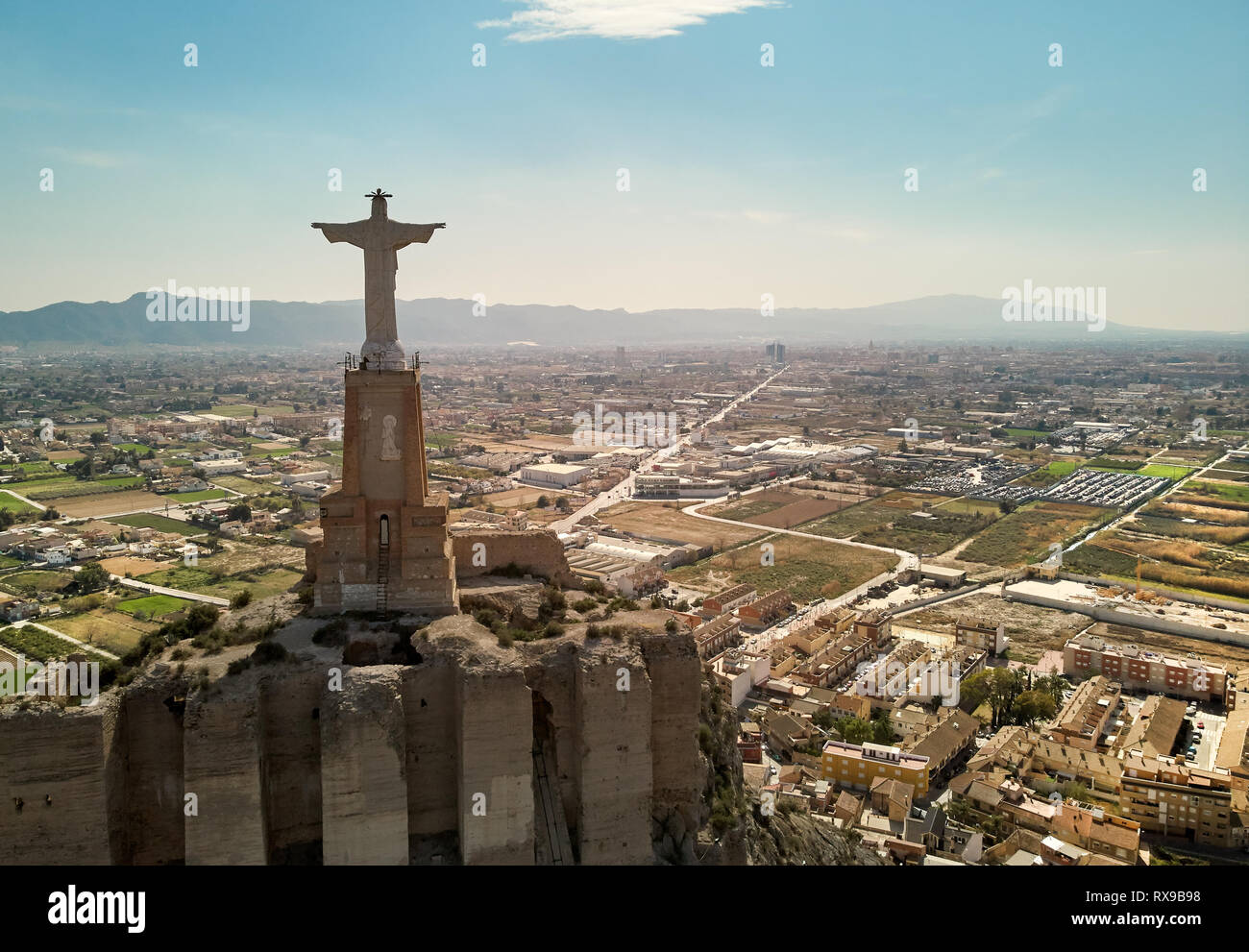 Aerial photography wide angle drone point of view Statue of Christ on a top of the limestone rock Monteagudo Castle fortress and cityscape of Murcia a - Stock Image