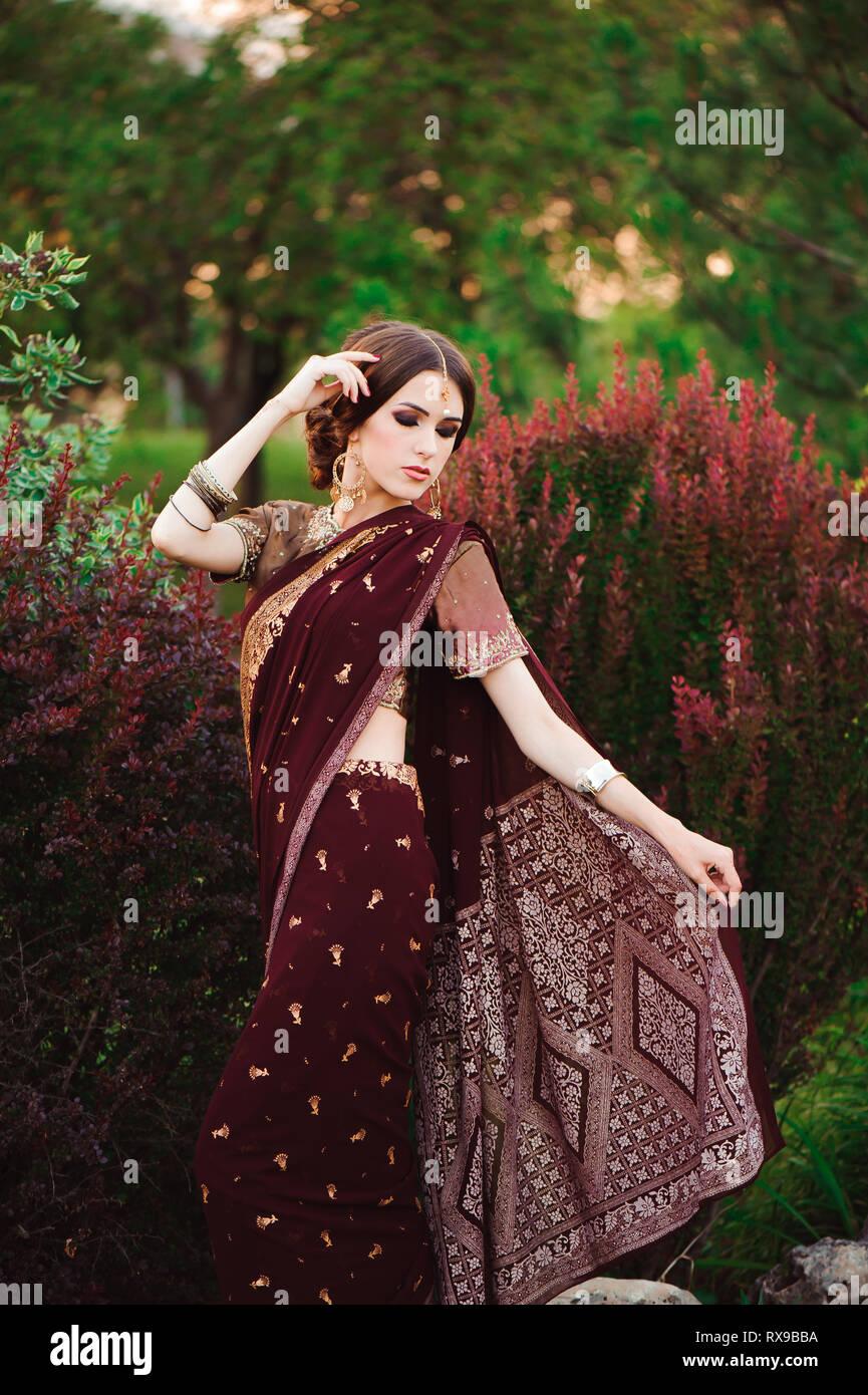 2b7f71a0c9 Portrait of beautiful indian girl. Young hindu woman model with tatoo  mehndi and kundan jewelry. Traditional costume saree.