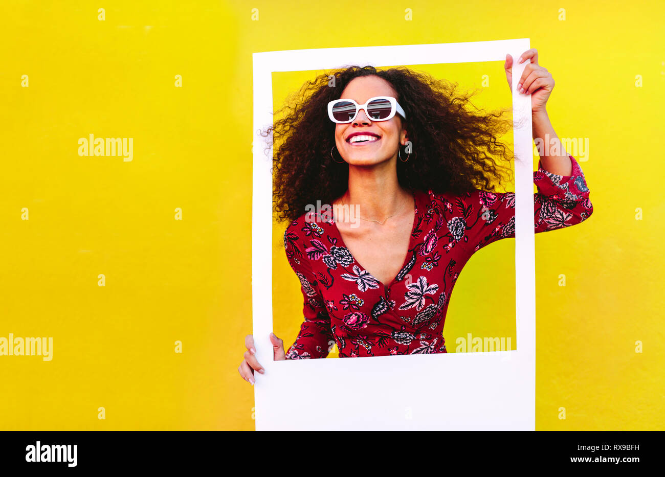 Mixed race woman with curly hair wearing sundress and sunglasses looking through blank photo frame. Beautiful female with big picture frame against ye - Stock Image