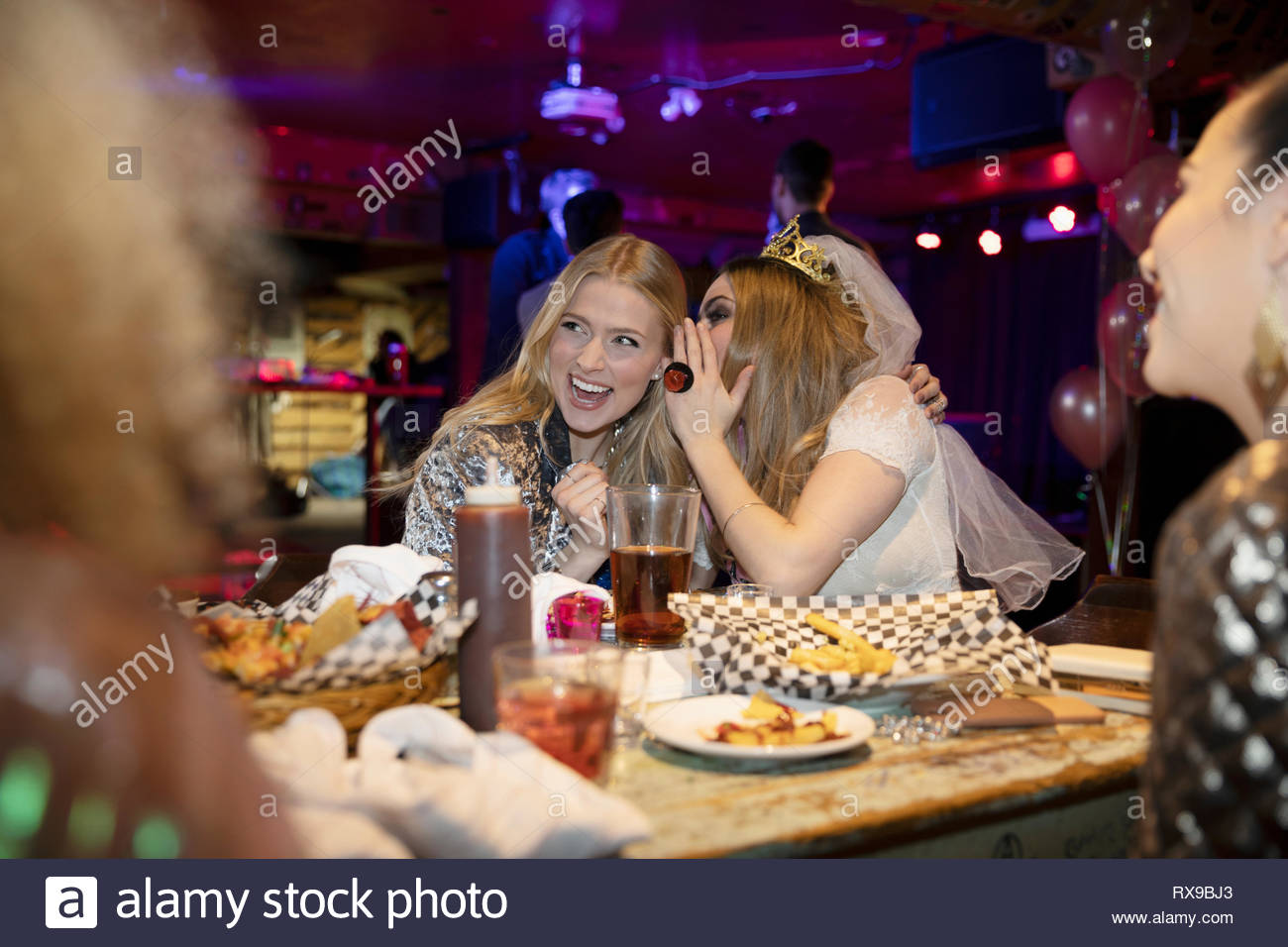 Bachelorette whispering in ear of friend at late night diner - Stock Image