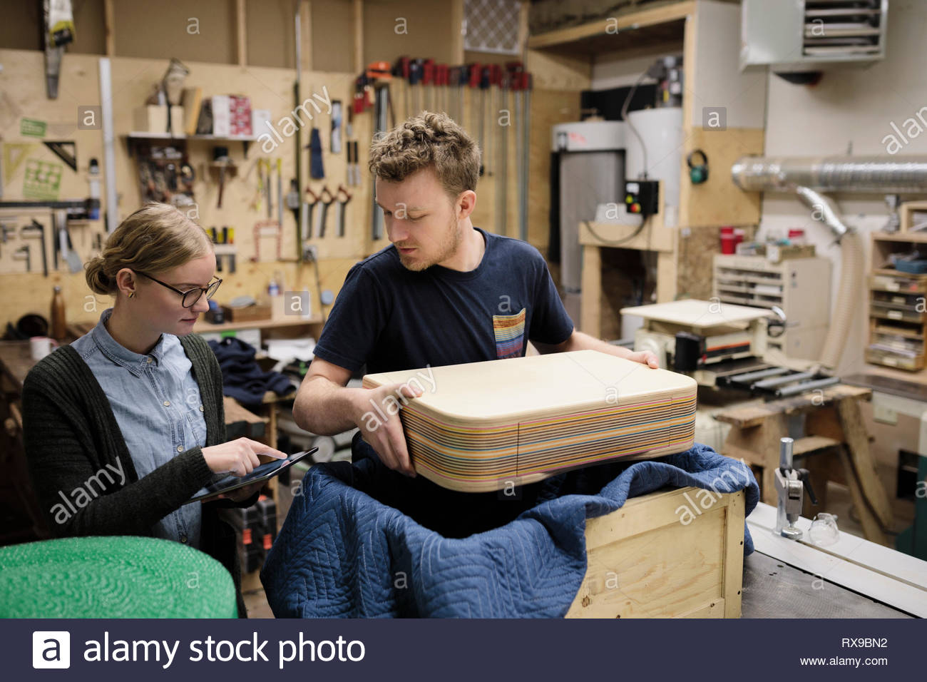 Artists with digital tablet packaging product in workshop - Stock Image