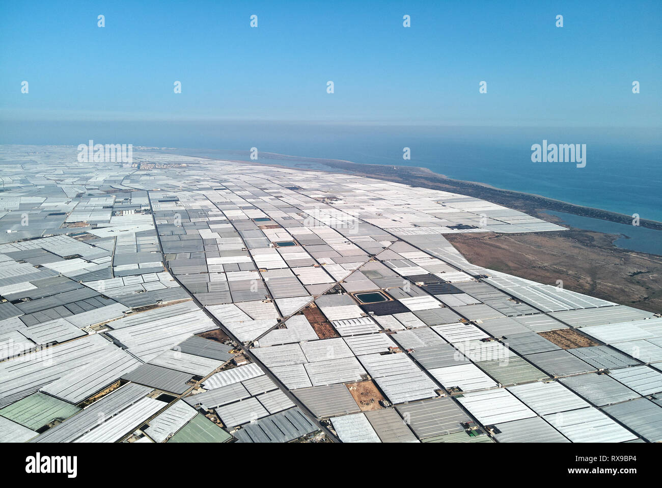 Aerial drone point of view lot of polythene plastic exterior greenhouses hothouses where cultivated fruits and vegetables in Almerimar near the sea, p - Stock Image