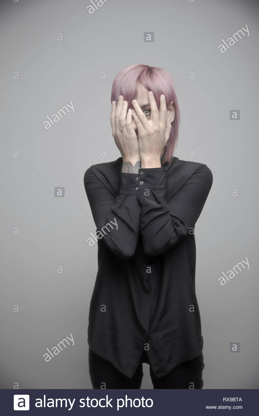 Portrait beautiful non-binary gender person with pink hair hiding behind hands - Stock Image