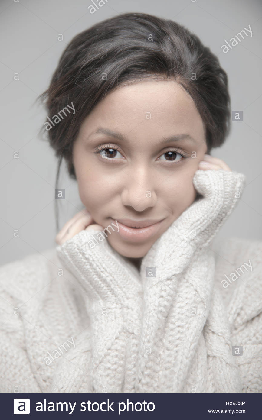 Portrait confident beautiful young Jamaican woman in sweater - Stock Image