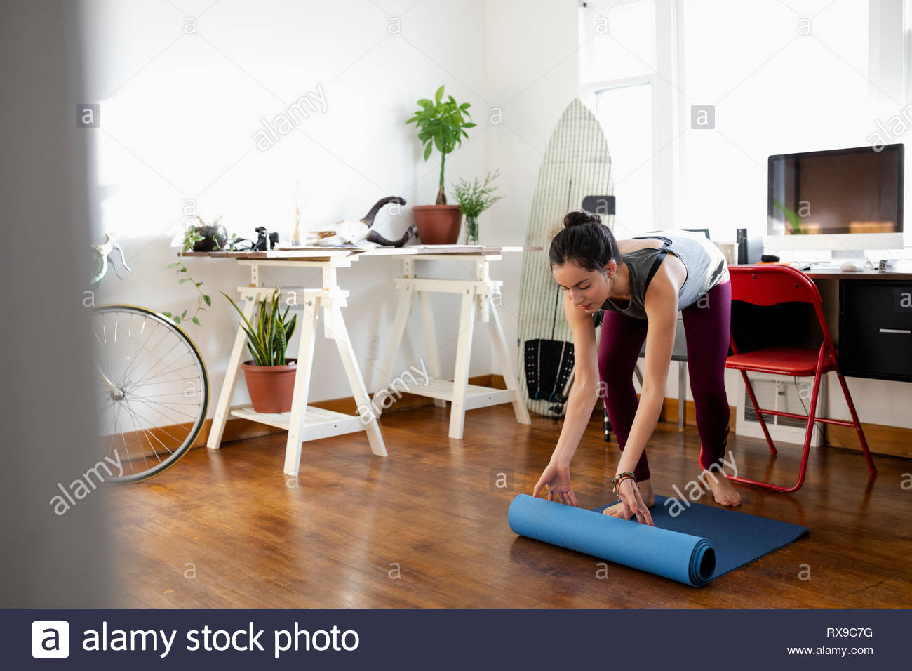 Young Latinx woman unrolling yoga mat in apartment - Stock Image