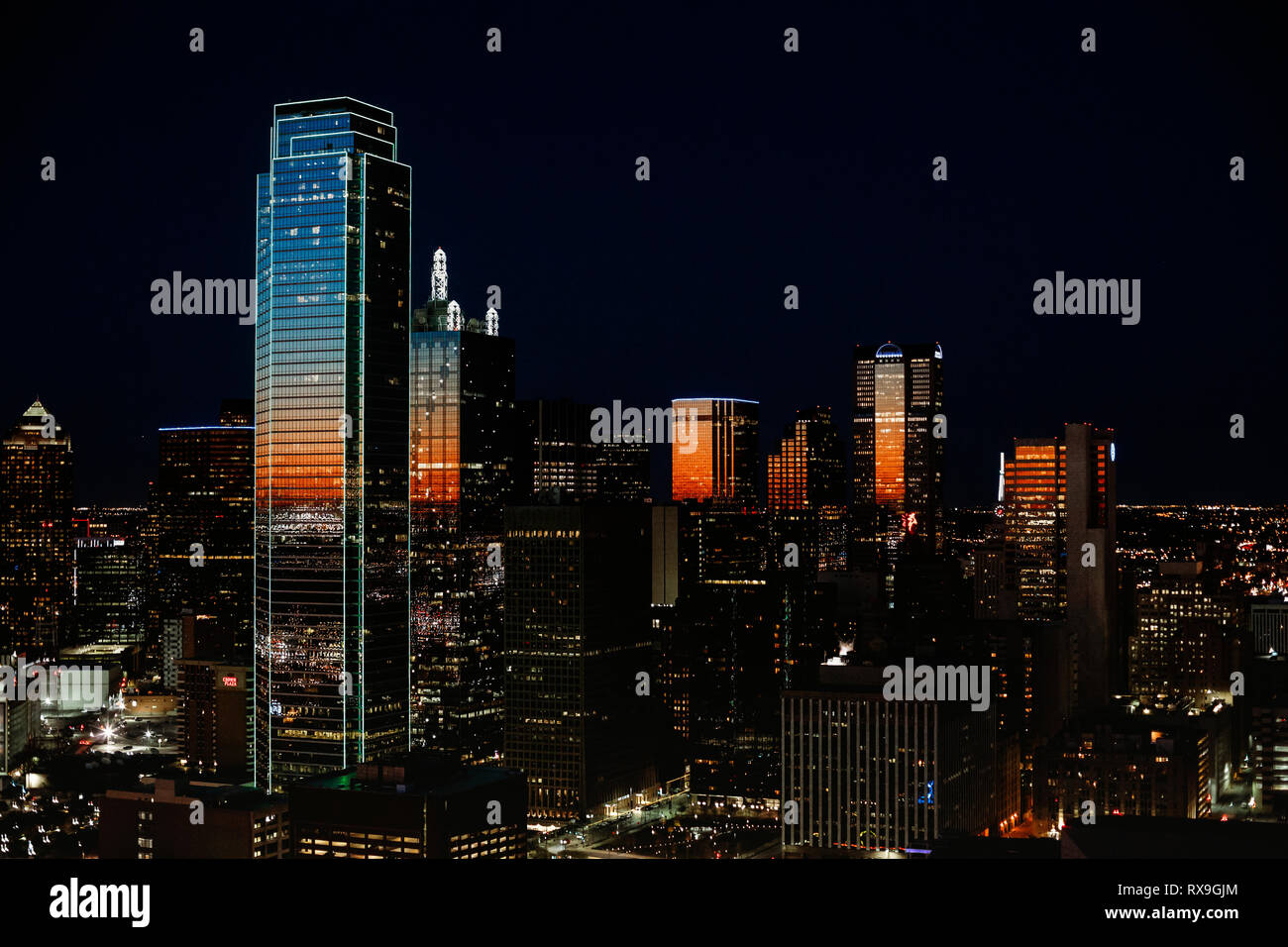 Digital composite image of illuminated modern buildings against sky at night - Stock Image
