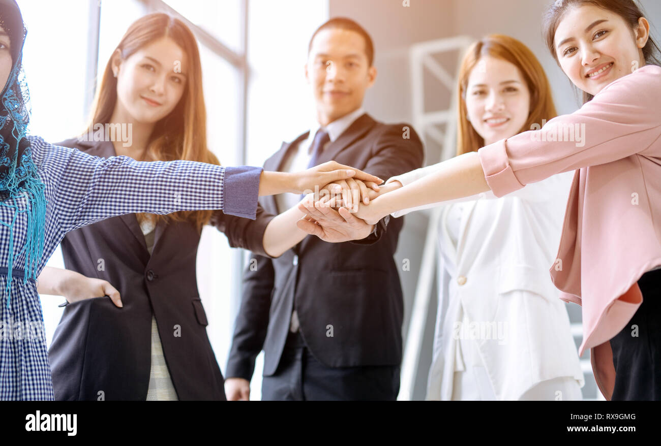 Business people in team stack hands together as unity and teamwork in office. young Asian businessman and group togetherness collaboration - Stock Image