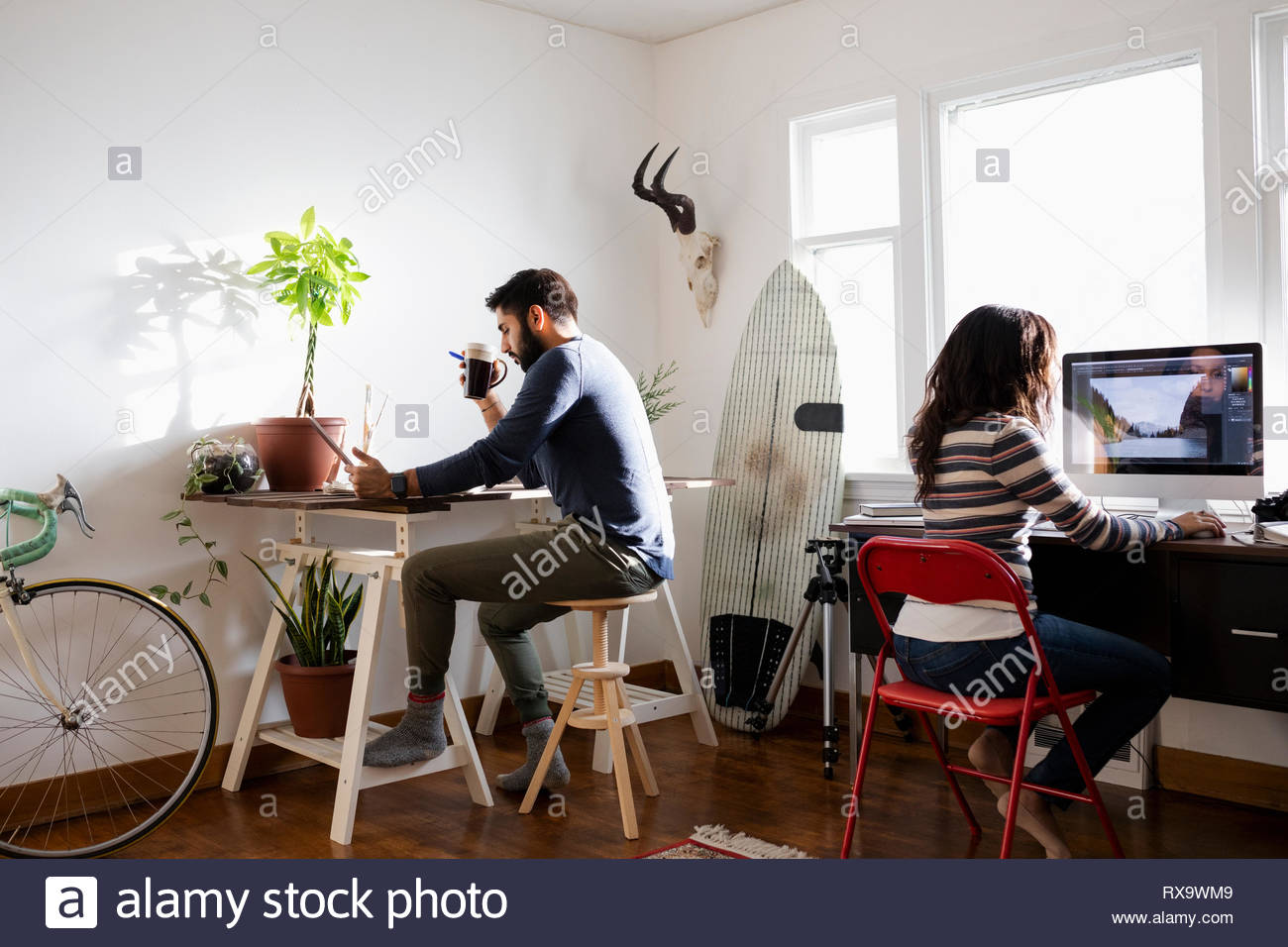 Creative freelance couple working in home office - Stock Image