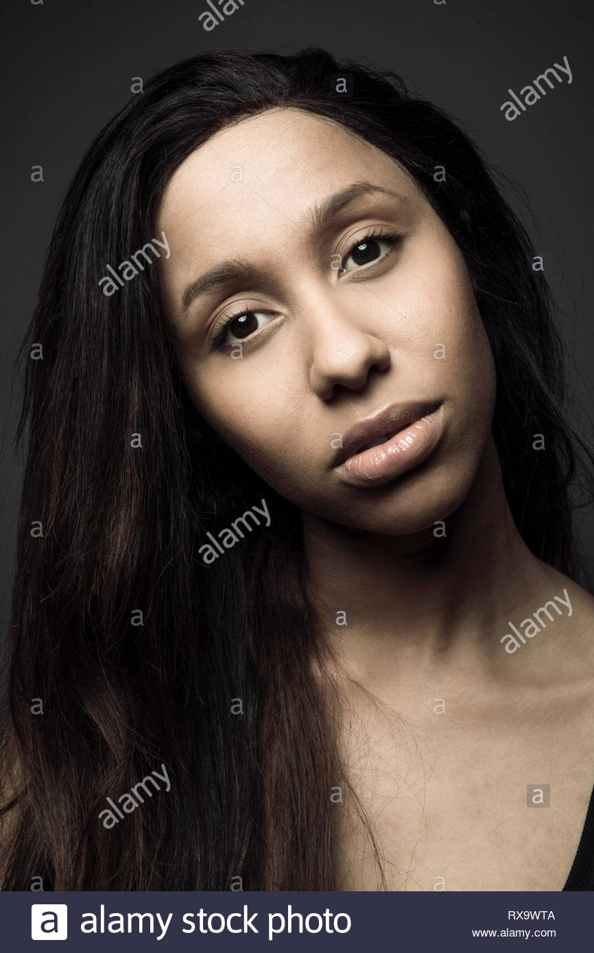 Portrait confident beautiful young Jamaican woman with long black hair - Stock Image