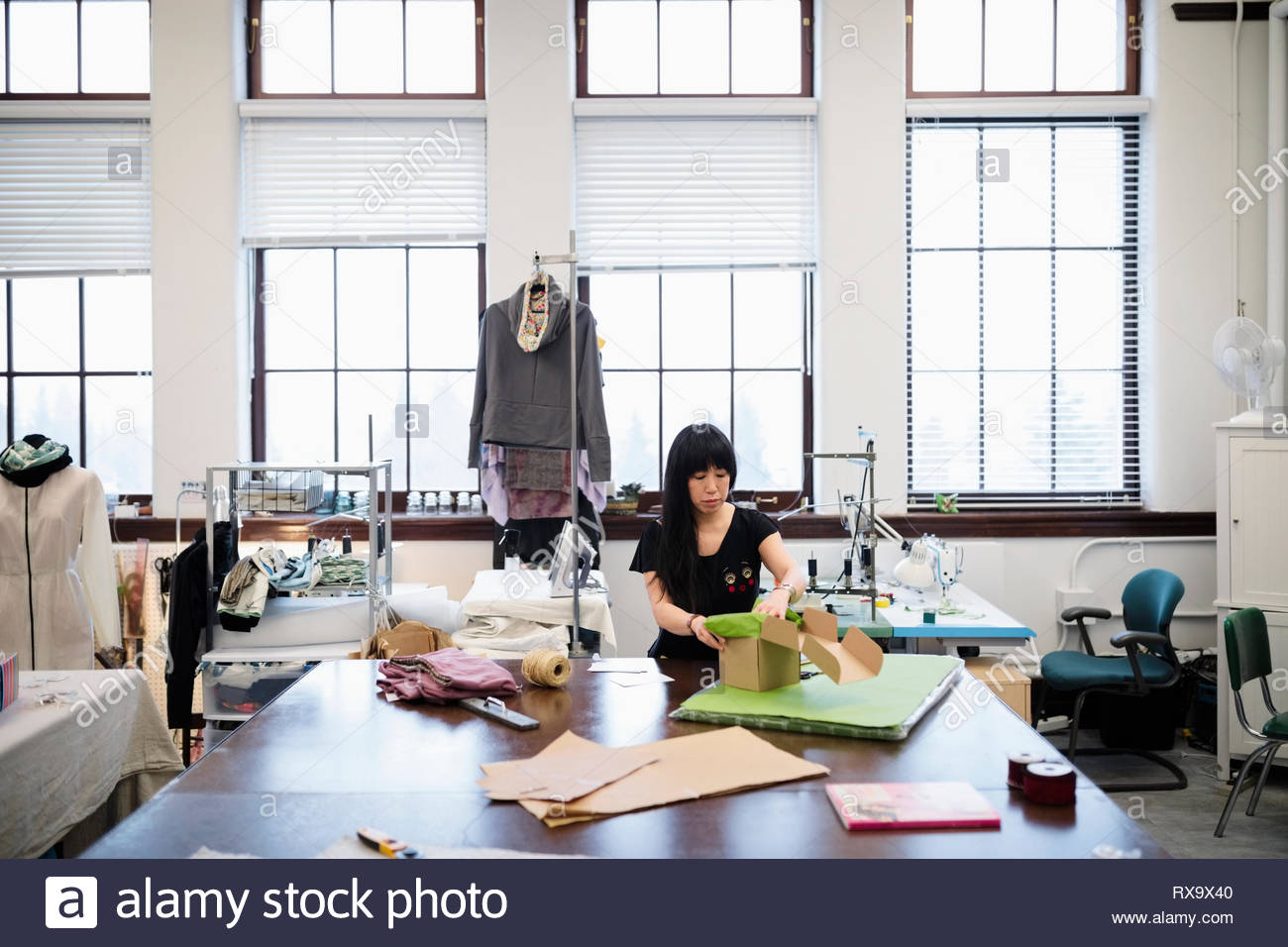 Female fashion designer packaging product in studio - Stock Image