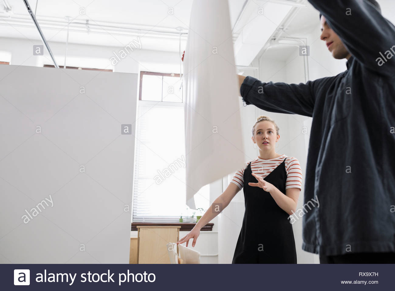 Artists hanging print in art gallery - Stock Image
