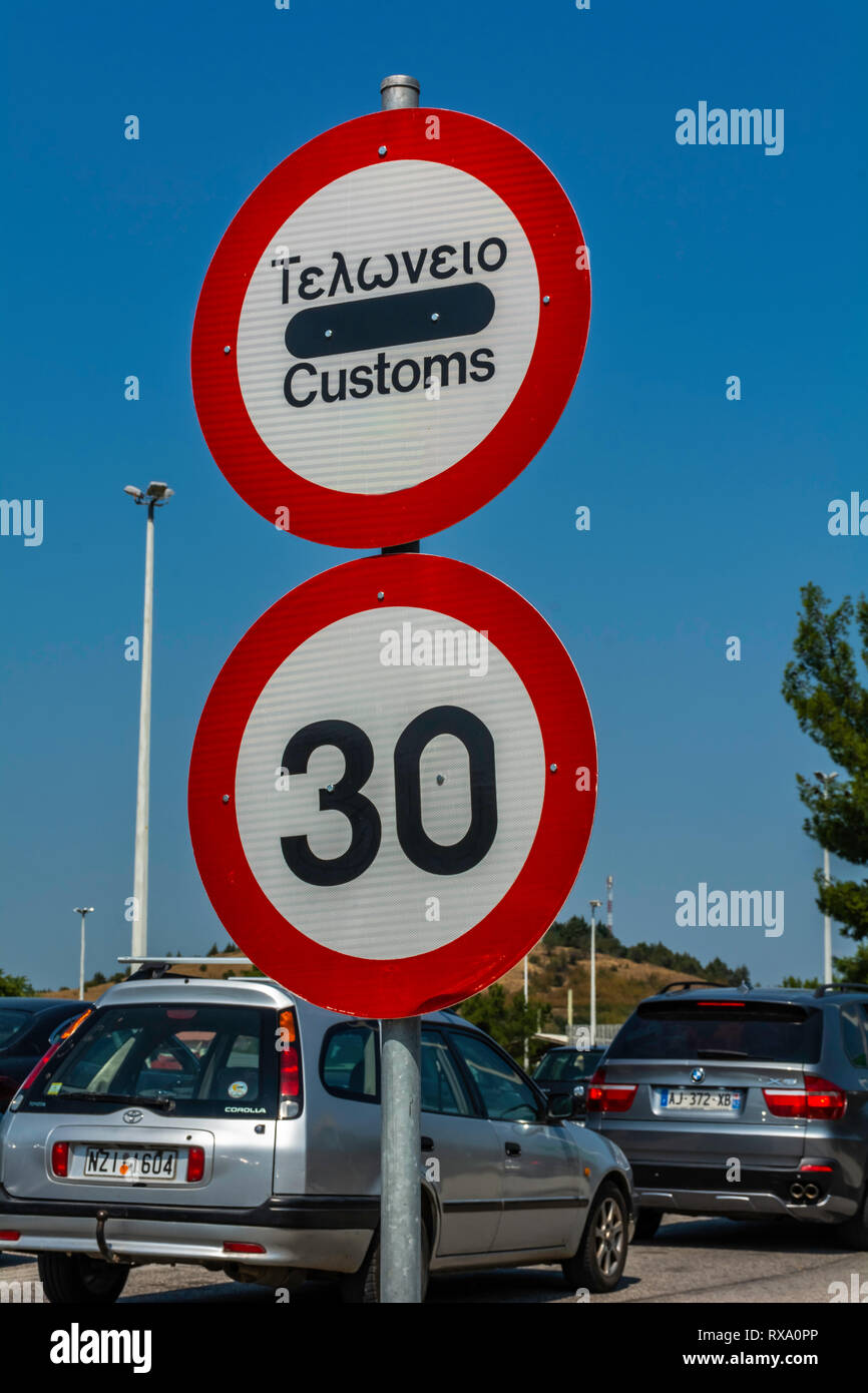 THESSALONIKI, GREECE - CIRCA AUGUST, 2018: Customs and speed limit signs informing travelers and tourists that they are approaching Greek state border - Stock Image