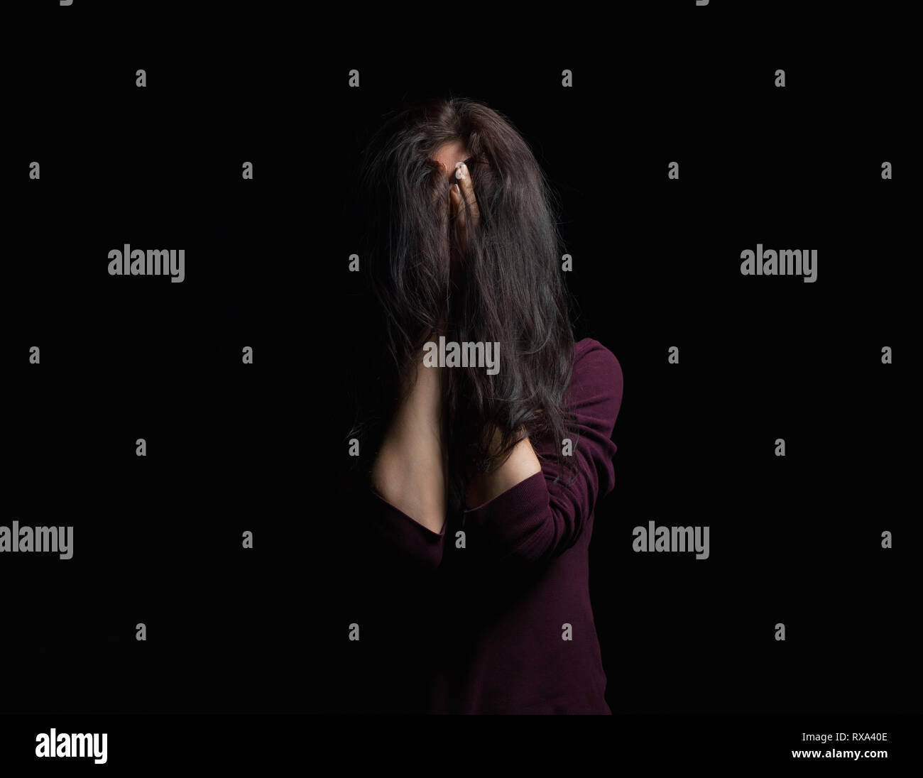 Woman covering face with hands while standing against black background - Stock Image