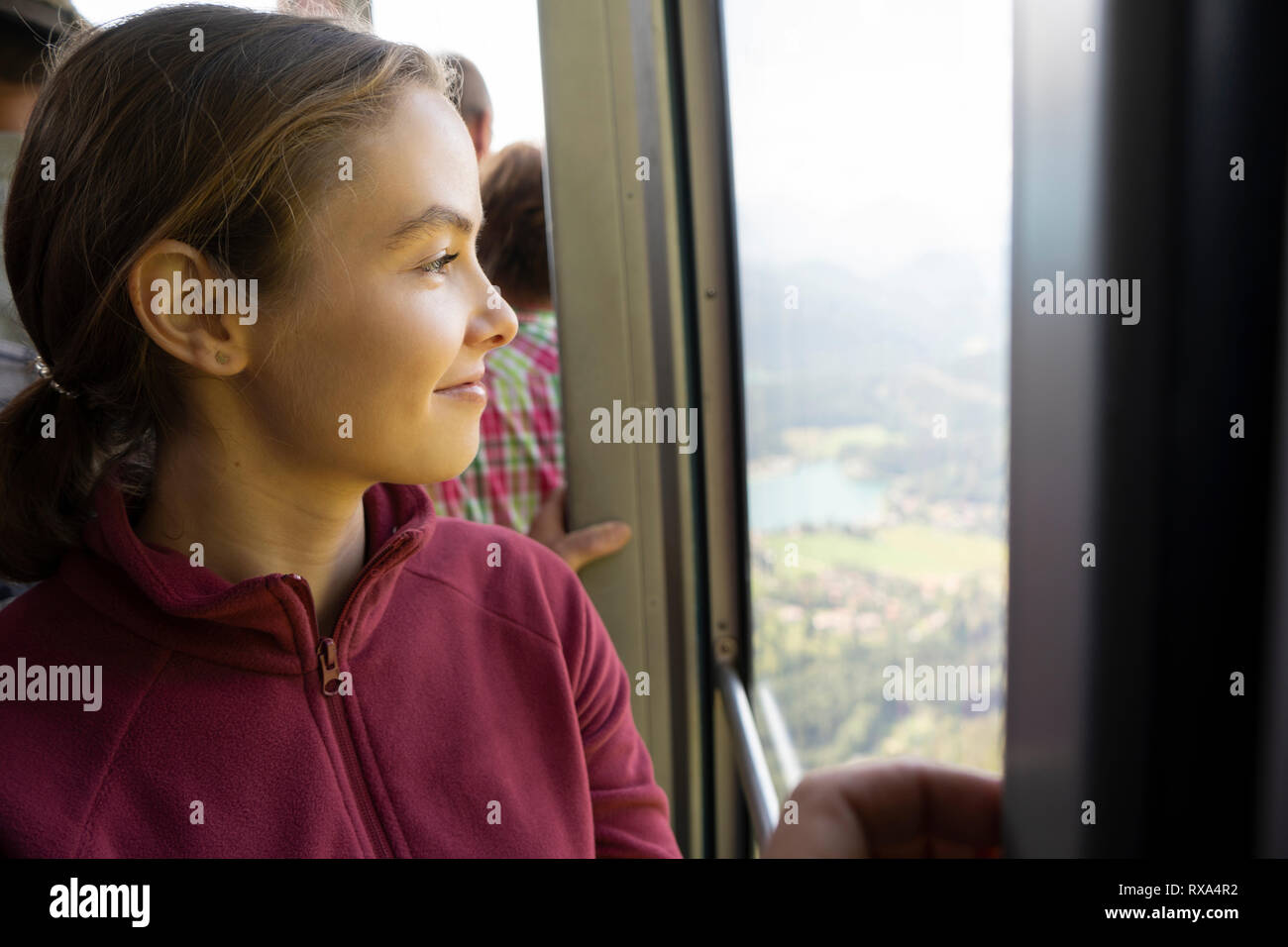 Smiling woman looking through window while traveling in overhead cable car - Stock Image