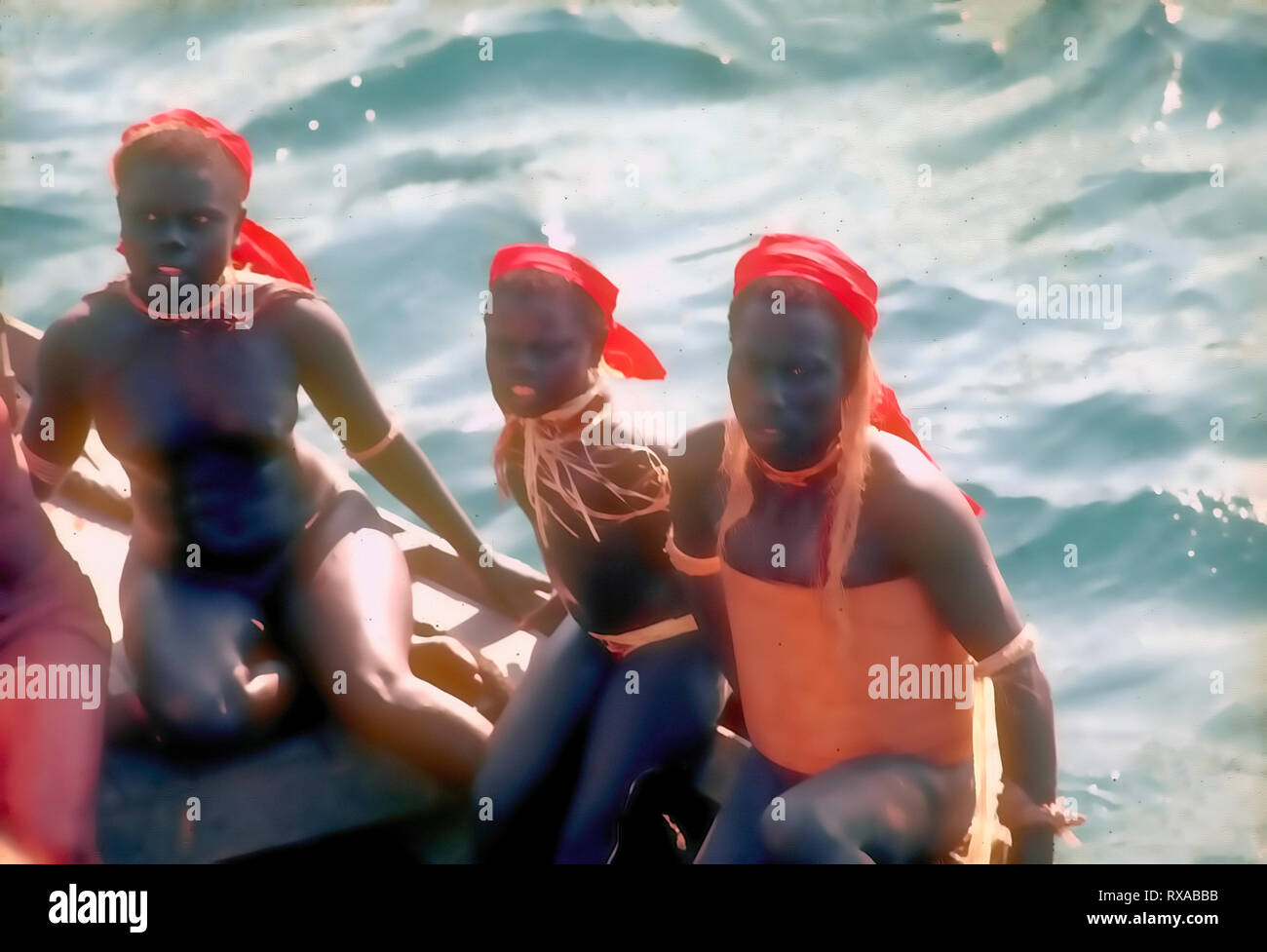 Young,Negrito,Jarwa group,sitting,on,Contact Party ,boat,returning,back,to, their,deep ,forest habitat,Middle Andaman Island,A&N Islands,India. - Stock Image