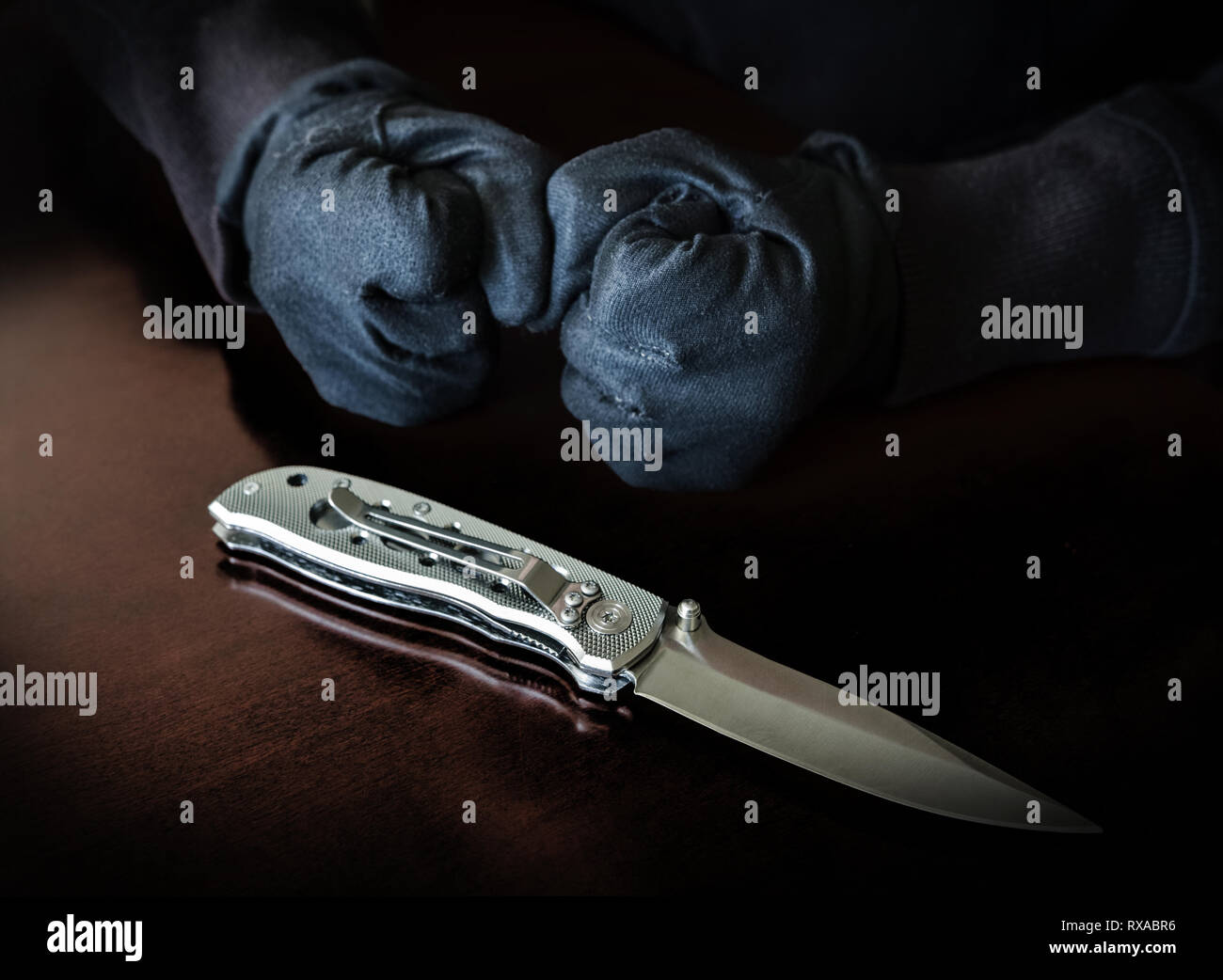 We see two fists clenched and gloved behind a folding knife with a pocket clip. Stock Photo