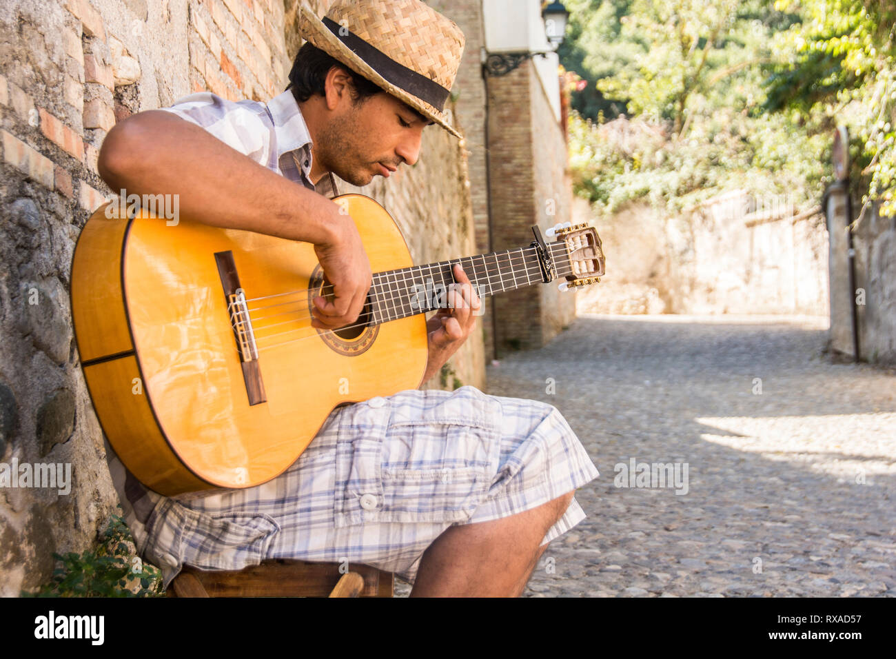 A young man in his early 20's playing Flamenco guitar in an alley; Granada, Spain. - Stock Image