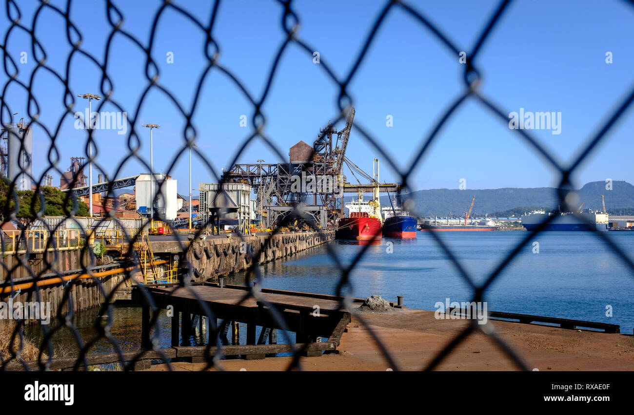 Ships loading coal and iron ore at industrial port taken through wire fence in foreground at an Australian Port, NSW. Trade war and tariffs concept - Stock Image