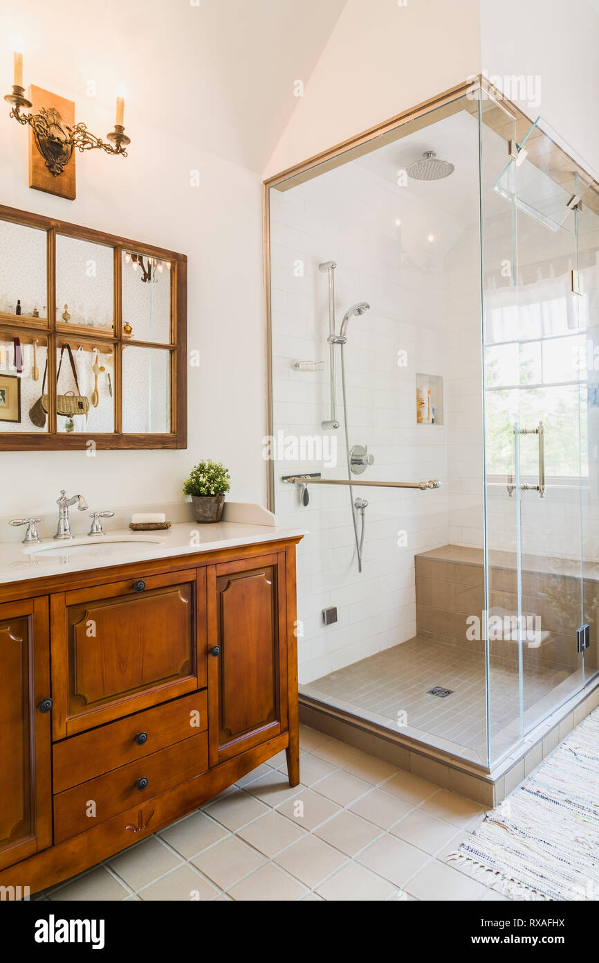 Antique Wooden Sink Cabinet With Quartz Countertop And Wall Mirror Glass Shower Stall In Ceramic Tile Floor En Suite On Upstairs Floor Inside A Leed Certified Country Home Quebec Canada This Image