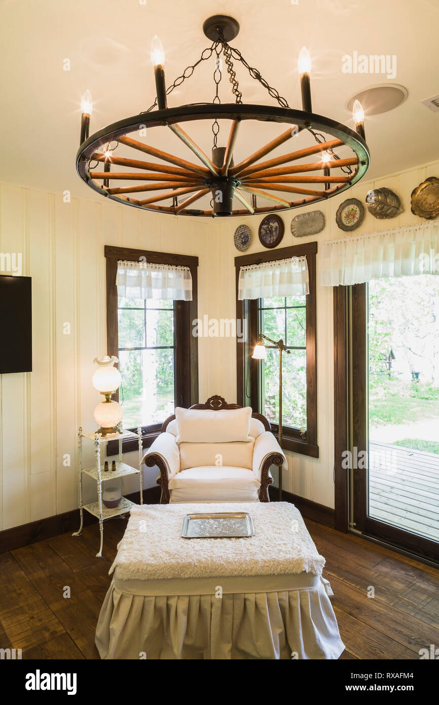 Study-Reading room with white upholstered antique armchair and pleated fabric-covered footstool, wagon wheel chandelier inside a LEED certified Countr - Stock Image