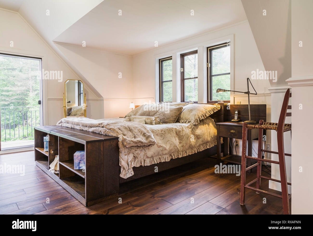 Wood Frame King Size Bed With Flowery Bedspread Brass Mirror And Antique Wooden High Chair In Master Bedroom On Upper Floor Inside A New Hampton Style Home Quebec Canada This Image Is Property