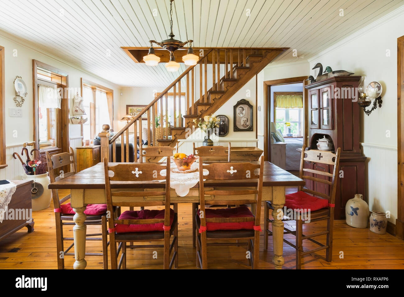 Cream and brown coloured wooden table and Lepine antique chairs with red cushions in dining room inside an old 1892 Canadiana cottage style home, Queb - Stock Image