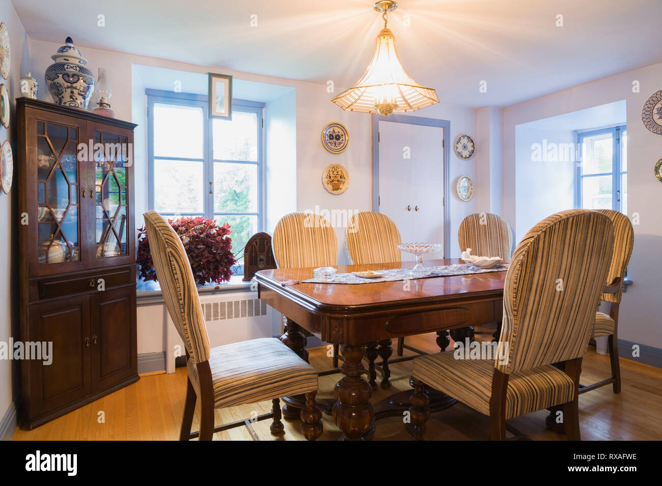 Walnut dining table with upholstered high-back chairs in dining room inside an old 1839 Canadiana fieldstone house, Quebec, Canada. This image is Prop - Stock Image