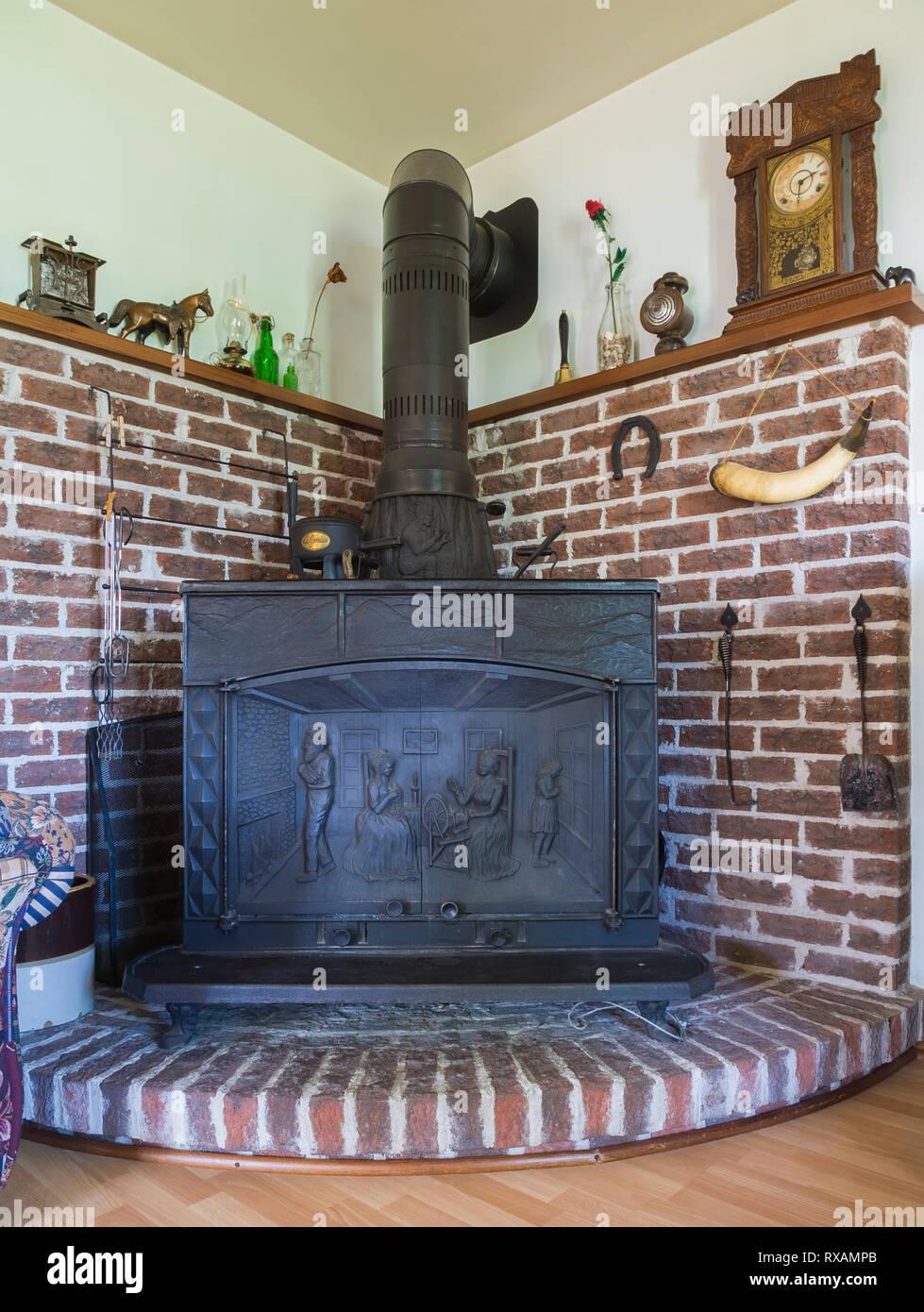 1977 Franklin reproduction wood stove mounted on elevated brick platform in living room inside an old 1927 Canadiana cottage style home, Quebec, Canad - Stock Image