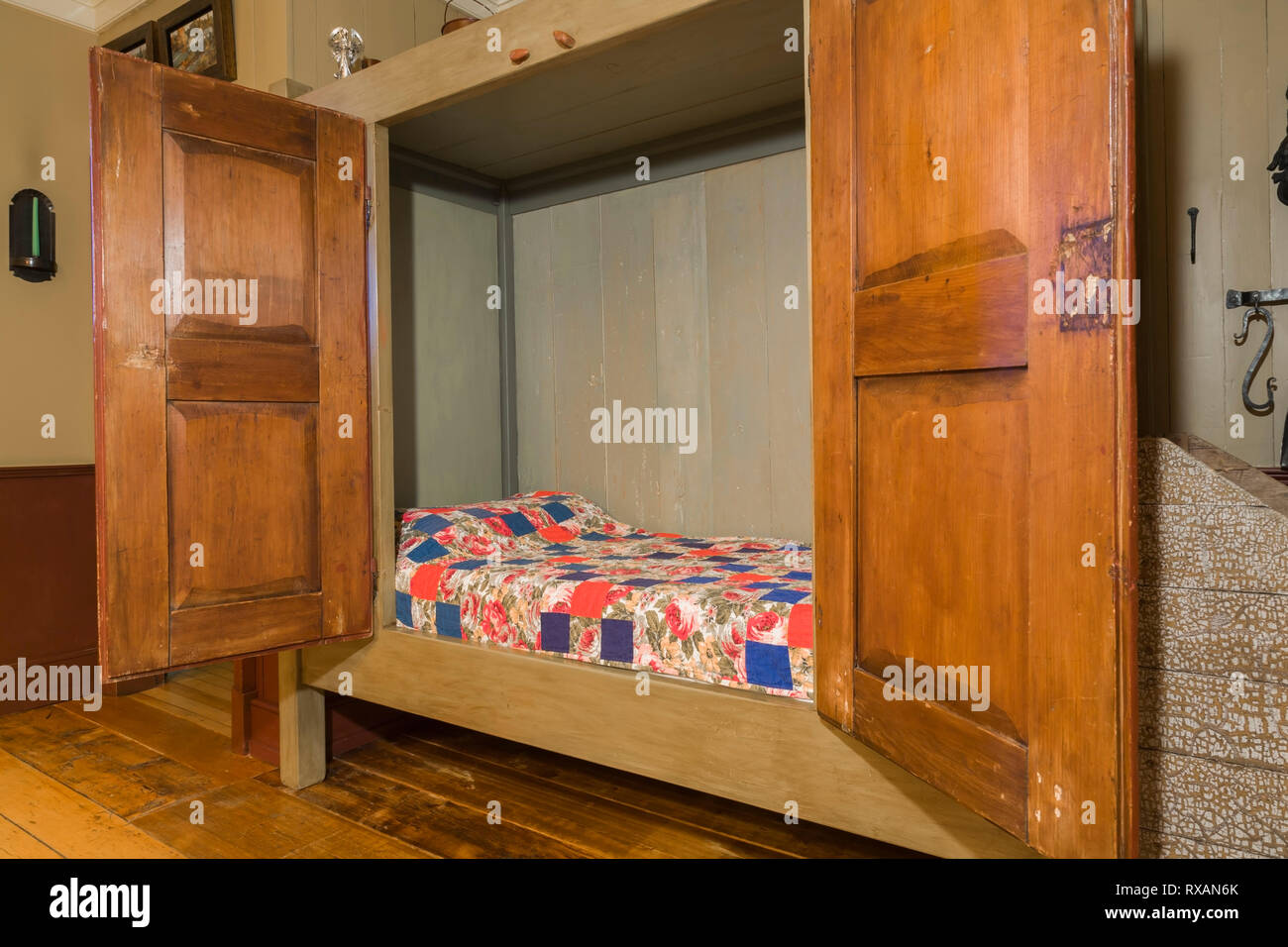 Single bed hidden in an old wooden armoire in the dining ...